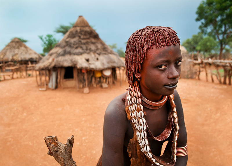This hamar woman is a second wife, this is symbolised by her two metal necklaces. The Hamar women who are not first wives have a really hard life, being more of a slave than a wife. Hamer women cover there body and hair with clay, butter and animal fat, and the more scars one has on her back, the higher her status.  Omo Valley, Southern Ethiopia, 2013.