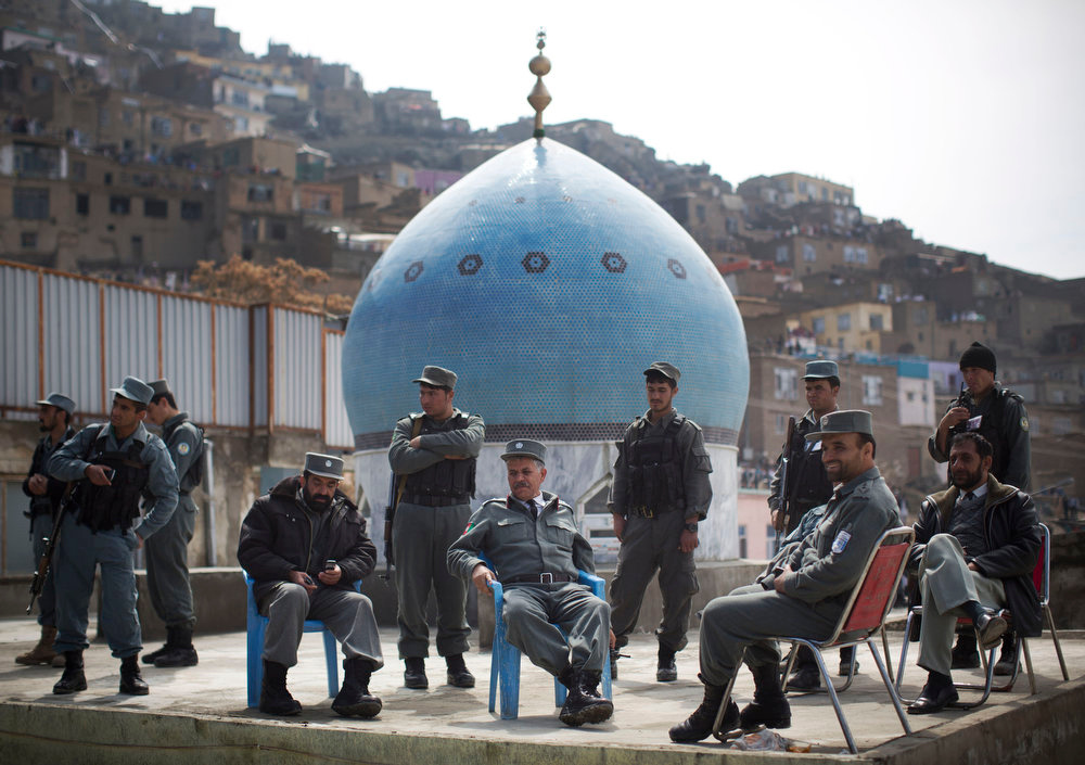 . Afghan policemen follow the raising of the holy flag at the Kart-e Sakhi mosque in Kabul, Afghanistan, Thursday, March 21, 2013. Afghanistan celebrates Nowruz, marking the first day of spring and the beginning of the year in the Iranian calendar. (AP Photo/Anja Niedringhaus)