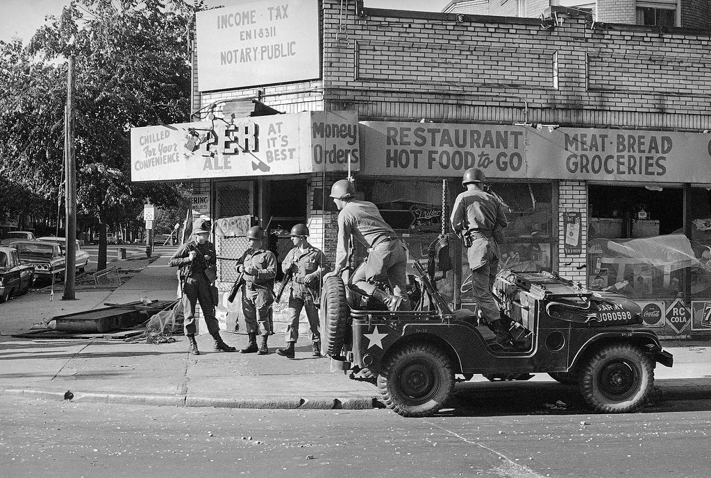 . Ohio National Guardsmen climb out of their jeep while three others standby to prevent looting in the riot-torn Hough area on the city?s east side in Cleveland, Ohio, July 20, 1966. The soldiers moved into the area about midnight, armed with rifles and machine guns. Police said there was so much looting during the past two days that they couldn?t keep count. (AP Photo/Julian C. Wilson)