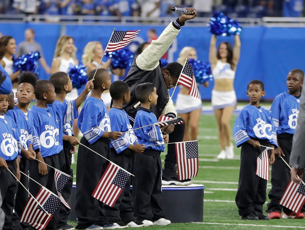 . National anthem singer Rico Lavelle bends to his knee, bows his head and raises his fist after singing the anthem before the first half of an NFL football game between the Detroit Lions and the Atlanta Falcons, Sunday, Sept. 24, 2017, in Detroit. (AP Photo/Carlos Osorio)