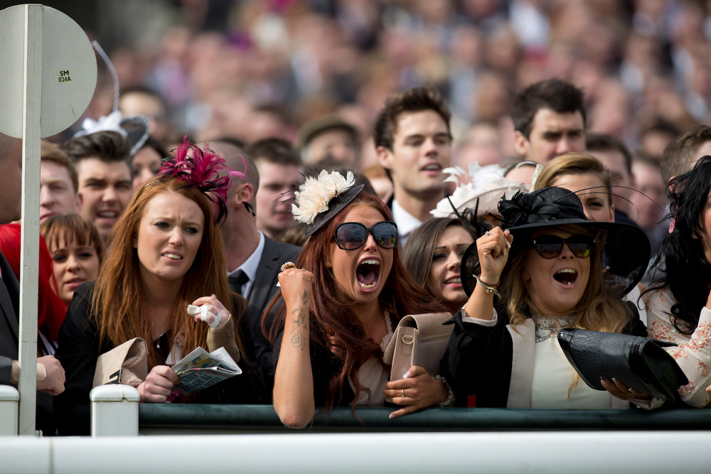 . Racegoers cheer on the horses during Ladies\' Day at Aintree Racecourse Liverpool, England, Friday, April 5, 2013. (AP Photo/Jon Super)