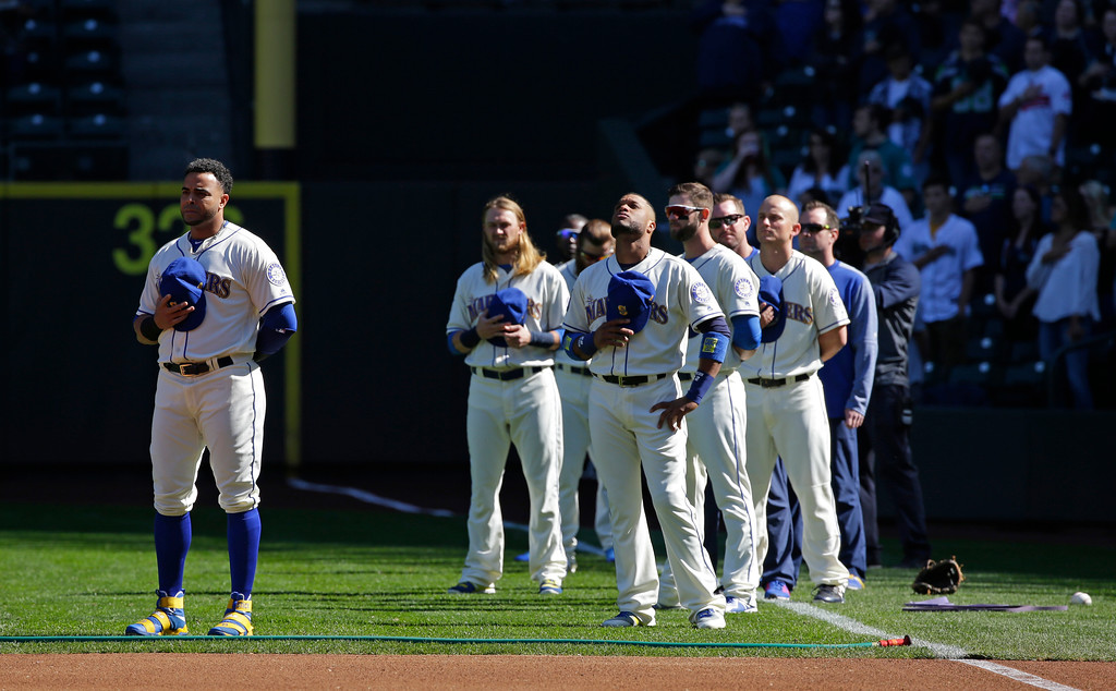 . Seattle Mariners players, including Nelson Cruz, left, stand during the singing of the national anthem before a baseball game against the Cleveland Indians, Sunday, Sept. 24, 2017, in Seattle. (AP Photo/Ted S. Warren)