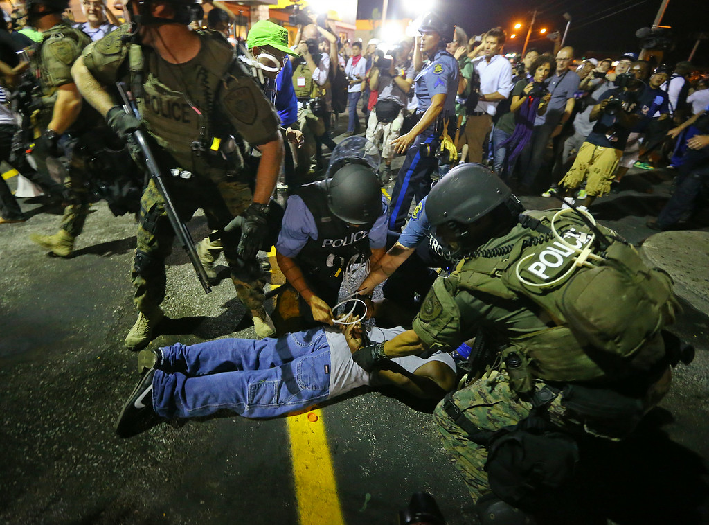 . Police handcuff a protester after rushing the crowd to arrest him on West Florissant Avenue in Ferguson, Mo. early Wednesday, Aug. 20, 2014. On Aug. 9, 2014, a white police officer fatally shot Michael Brown, an unarmed black 18-year old, in the St. Louis suburb. (AP Photo/Atlanta Journal-Constitution, Curtis Compton)