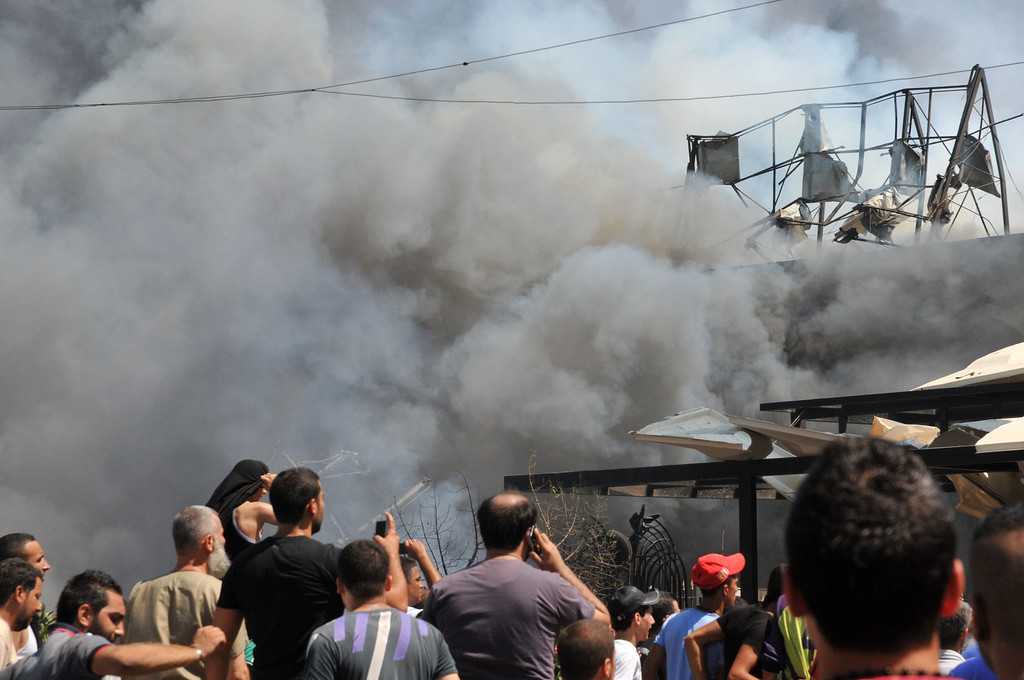 . Smoke rises above people gathering near al-taqwa mosque on the site of a powerful explosion in the northern Lebanese city of Tripoli on August 23, 2013.  AFP PHOTO  IBRAHIM  CHALHOUB/AFP/Getty Images