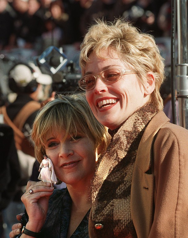 """. Carrie Fisher, left, holds up a tiny Princess Leah doll before going into the world premiere of \""""Star Wars Special Edition\"""" with her friend Sharon Stone, right, Saturday, Jan. 18, 1997, in the Westwood section of Los Angeles.  Fisher played the character of Princess Leah in the movie which was first released 20 years ago. (AP Photo/Rene Macura)"""