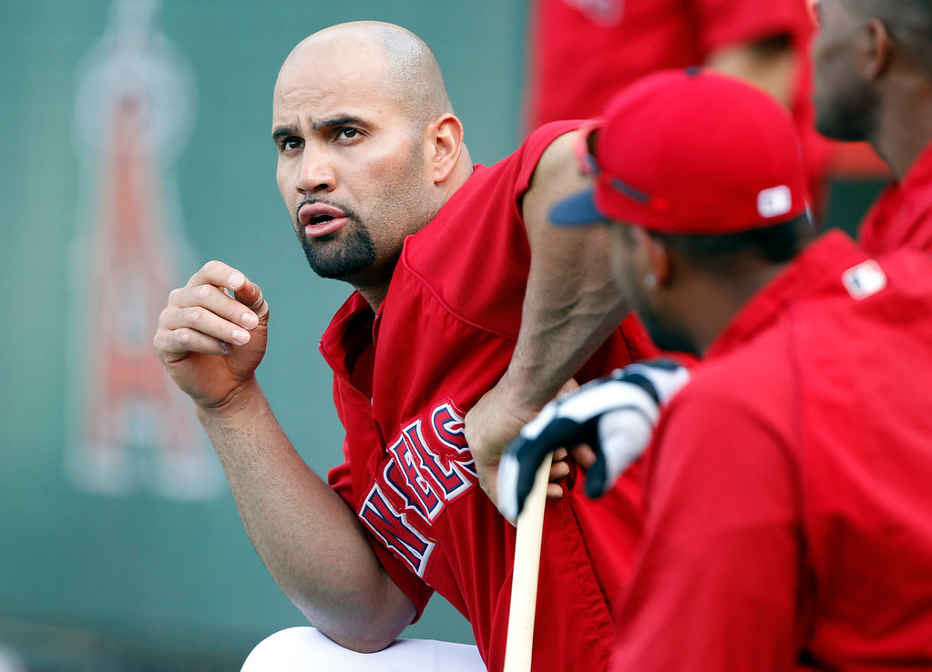 . Los Angeles Angels designated hitter Albert Pujols, left, talks to teammates prior to taking batting practice before a baseball game Seattle Mariners Tuesday, May 21, 2013 in Anaheim.    (AP Photo/Alex Gallardo)