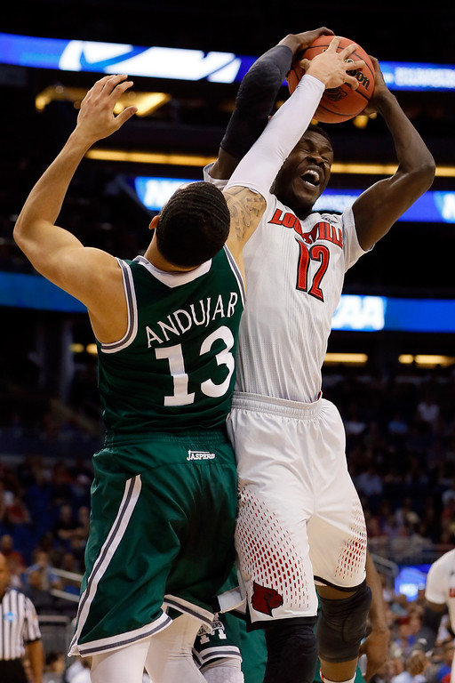 . Emmy Andujar #13 of the Manhattan Jaspers fights for a rebound against Mangok Mathiang #12 of the Louisville Cardinals during the second round of the 2014 NCAA Men\'s Basketball Tournament at Amway Center on March 20, 2014 in Orlando, Florida.  (Photo by Kevin C. Cox/Getty Images)