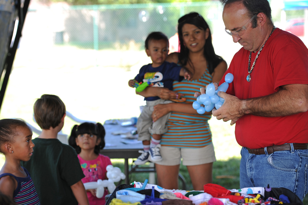. Gary Jones, right, with Miss Kiddee and Friends, makes balloon animals for kids  at Buckley Air Force base in Aurora, CO on August 4, 2013.  The event was part of the 140th Wing Family Day for members of the Colorado National Guard.  Much of the money raised during the day goes to the Colorado National Guard Family Support System that helps take care of families when their loved ones have been deployed.  The Salvation Army was on hand to show their continued support for the armed services.  Photo by Helen H. Richardson/The Denver Post)