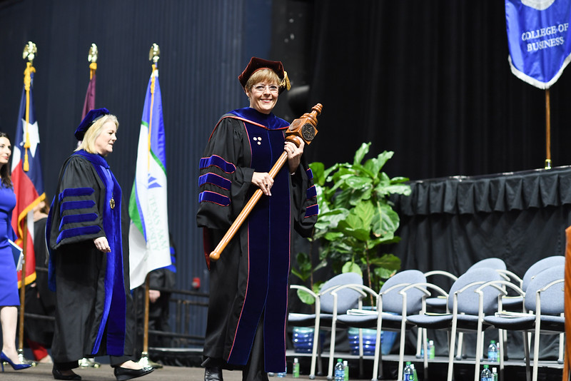 Dr. Cheri McCollough, Professor of Science Education, carries the ceremonial mace during opening ceremonies.