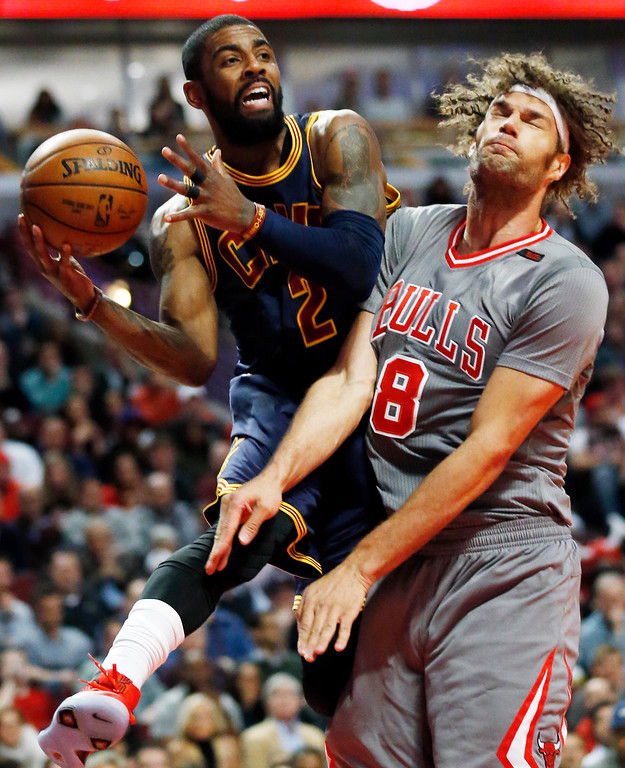 . Cleveland Cavaliers guard Kyrie Irving, left, looks to pass against Chicago Bulls center Robin Lopez during the first half of an NBA basketball game Thursday, March 30, 2017, in Chicago. (AP Photo/Nam Y. Huh)