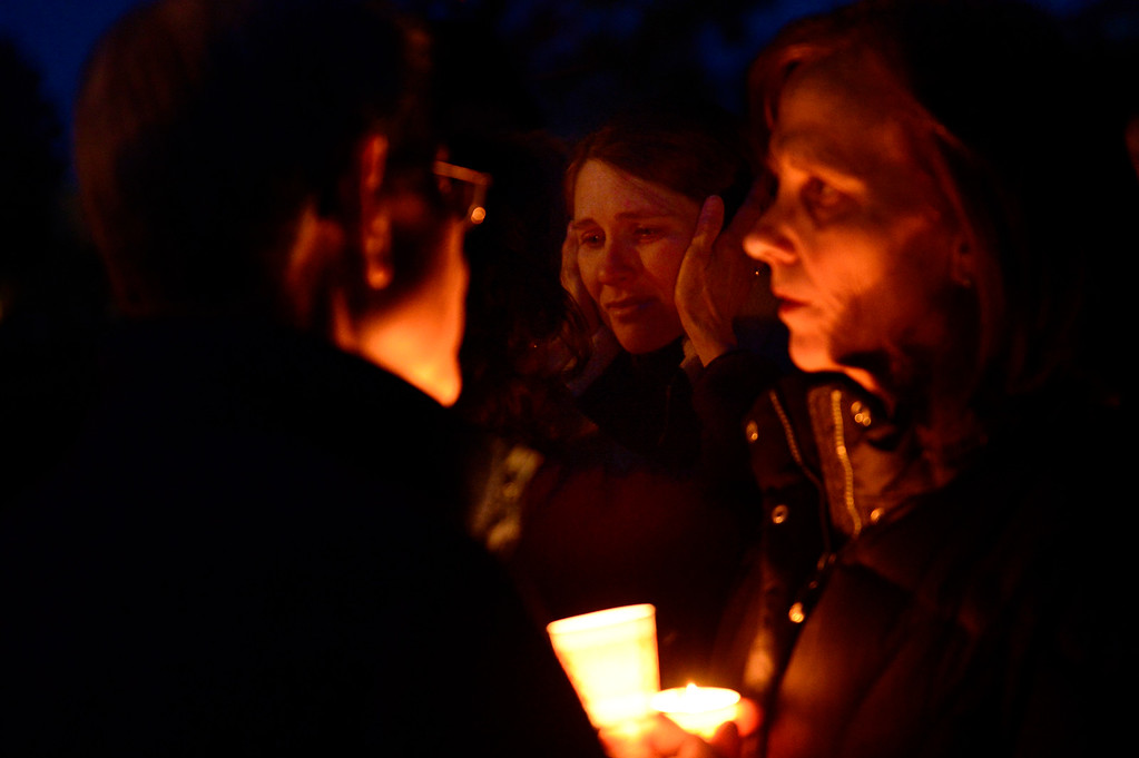 . A family member of Dr. Kenneth Atkinson gets embraced after a vigil for Dr. Kenneth Atkinson on April 5, 2016 in Centennial, Colorado. Close to 400 people showed up to pay their respects to Dr. Atkinson, who lost his life trying to protect a woman whose husband shot her. (Photo by Brent Lewis/The Denver Post)