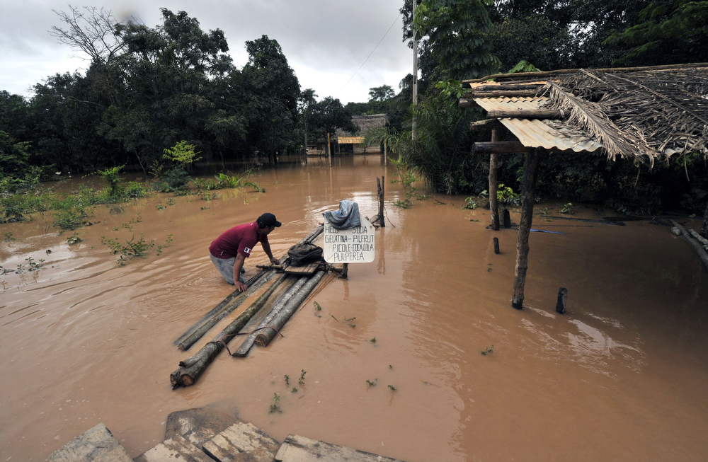 . A man wades through his backyard, flooded by the overflowing of the Beni river following heavy rains hitting the country, in Reyes, department of Beni, northeast Bolivia, on February 2, 2014. (AIZAR RALDES/AFP/Getty Images)