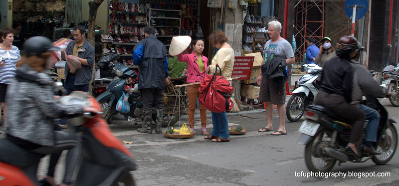 Woman hustling money from unsuspecting tourists in Hanoi, Vietnam in January 2012