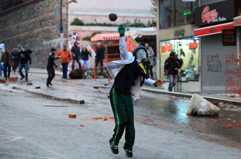 . A protestor wearing a gas mask throws a stone onto police during clashes with riot police after the funeral of Berkin Elvan on March 12, 2014 in Istanbul.  Riot police fired tear gas and water cannon at protesters in Ankara and Istanbul on Wednesday as tens of thousands took to the streets to mourn a teenage boy who died from injuries suffered in last year\'s anti-government protests. In the Turkish capital, police clashed with demonstrators as they tried to stop traffic, making a number of arrests and leaving several injured. (MIRA/AFP/Getty Images)