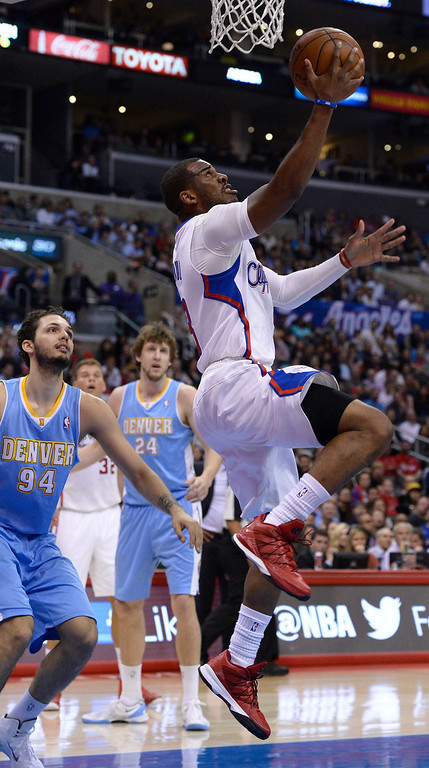 . Clippers#3 Chris Paul lays the ball up while Nuggets #94 Evan Fournier and #24 Jan Vesely look on in the first half. The Los Angeles Clippers took on the Denver Nuggets in a regular season NBA game. Los Angeles, CA. 4/15/2014(Photo by John McCoy / Los Angeles Daily News)