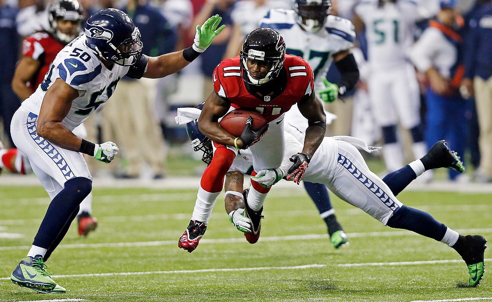 Description of . Atlanta Falcons wide receiver Julio Jones (11) works against Seattle Seahawks outside linebacker K.J. Wright (50) and free safety Earl Thomas (29) during the second half of an NFC divisional playoff NFL football game Sunday, Jan. 13, 2013, in Atlanta. (AP Photo/John Bazemore)