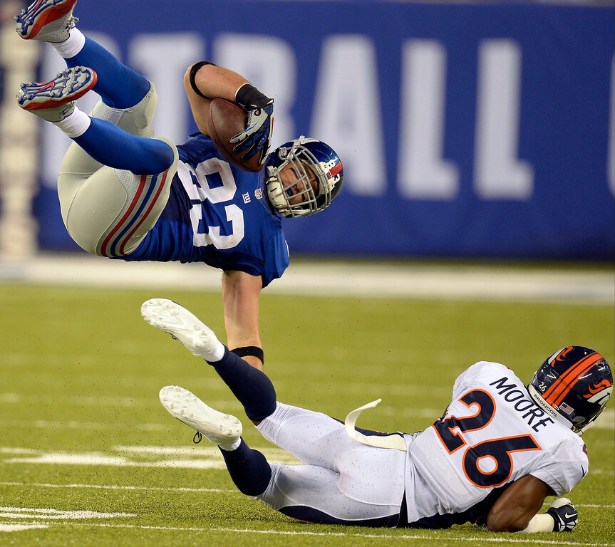 . Denver Broncos free safety Rahim Moore (26) hits New York Giants tight end Brandon Myers (83) low to send him flying during the fourth quarter September 15, 2013 MetLife Stadium. (Photo by John Leyba/The Denver Post)