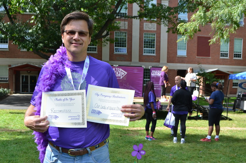 """Ed holding up the certificates that Razzmatazz team received for their fundraising efforts.  Razzmatazz won """"rookie of the year"""" award for best new team and Our Lady of Grace was recognized as sponsor with largest donations collected."""