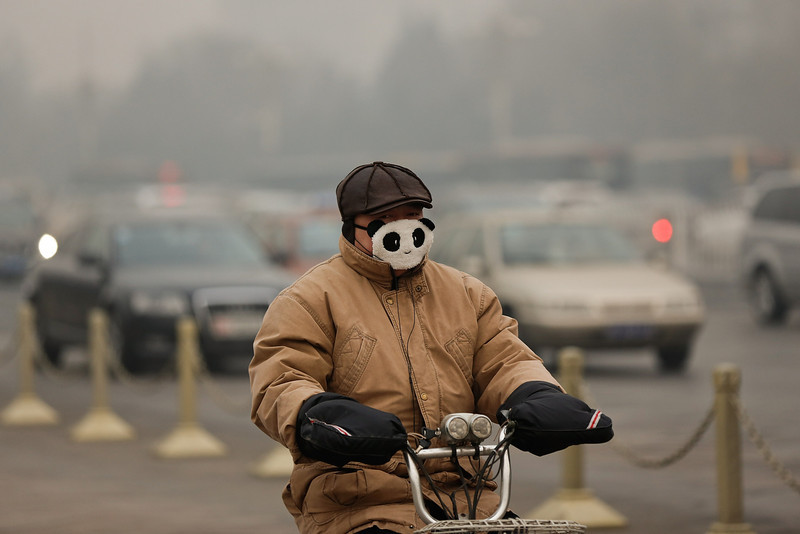 . A man wearing the mask rides a bicycle during severe pollution on February 25, 2014 in Beijing, China. The air pollution has caused an increase in the number of people seeking hospital treatment for respiratory problems and the public are asked to avoid outdoor activities.  (Photo by Lintao Zhang/Getty Images)
