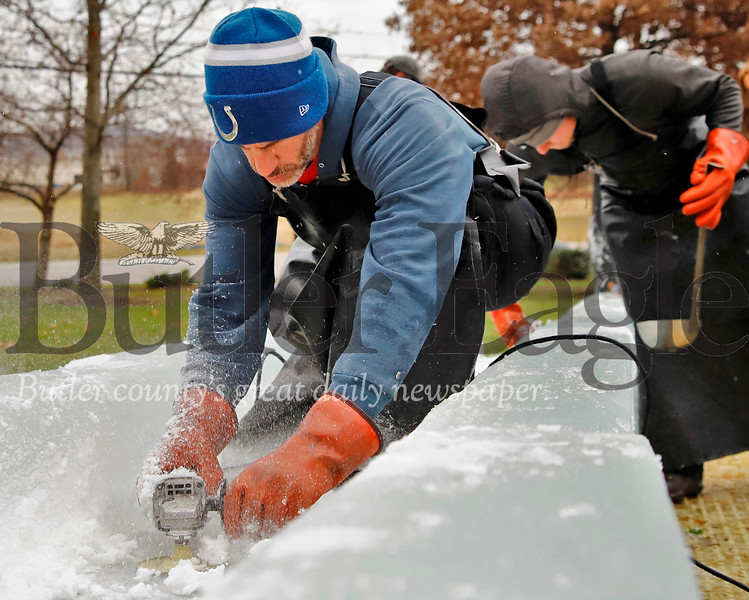 David DeFloria of DiMartino Ice Company puts the finishing touches on the ice slide being built for  for for Cranberry Township's Santa's First Stop Eagle North Pole Ice Festival Friday. Seb Foltz/Butler Eagle