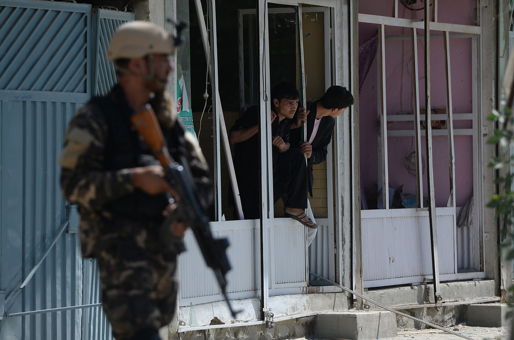 . Afghan shopkeepers look at the site of a suicide attack in Kabul on May 16, 2013.  AFP PHOTO/ Massoud HOSSAINI/AFP/Getty Images