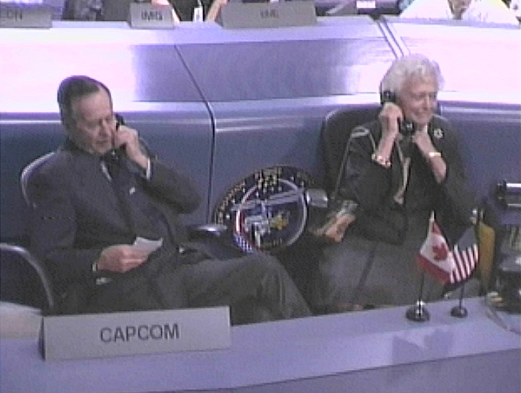 . Former U.S. President George Bush, left, and his wife, Barbara Bush talk to the crew aboard the International space station from the CAPCOM desk in mission control in Houston Monday, Feb. 3, 2003.   The Bushes paid a visit to NASA to offer their support to the crew and NASA workers. (AP Photo/NASA TV)