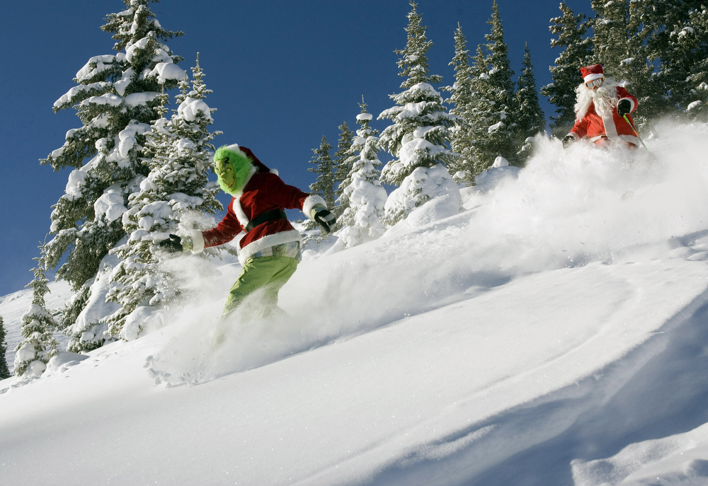 Description of . Austin Gibney of Mt. Crested Butte, Colo. dressed as The Grinch snowboarding as he steals the powder from skier Ben Somrak of Crested Butte, dressed as Santa Claus,  as they both enjoy the first day of winter at Crested Butte, Colo., on Sat., Dec. 22, 2007.  (Photo/Nathan Bilow, courtesy of Crested Butte Mountain Resort)