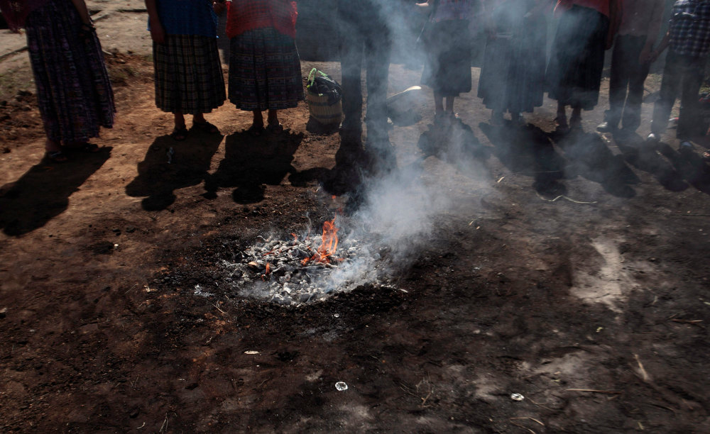 Description of . Indigenous people stand around the sacred fire during the mass of
