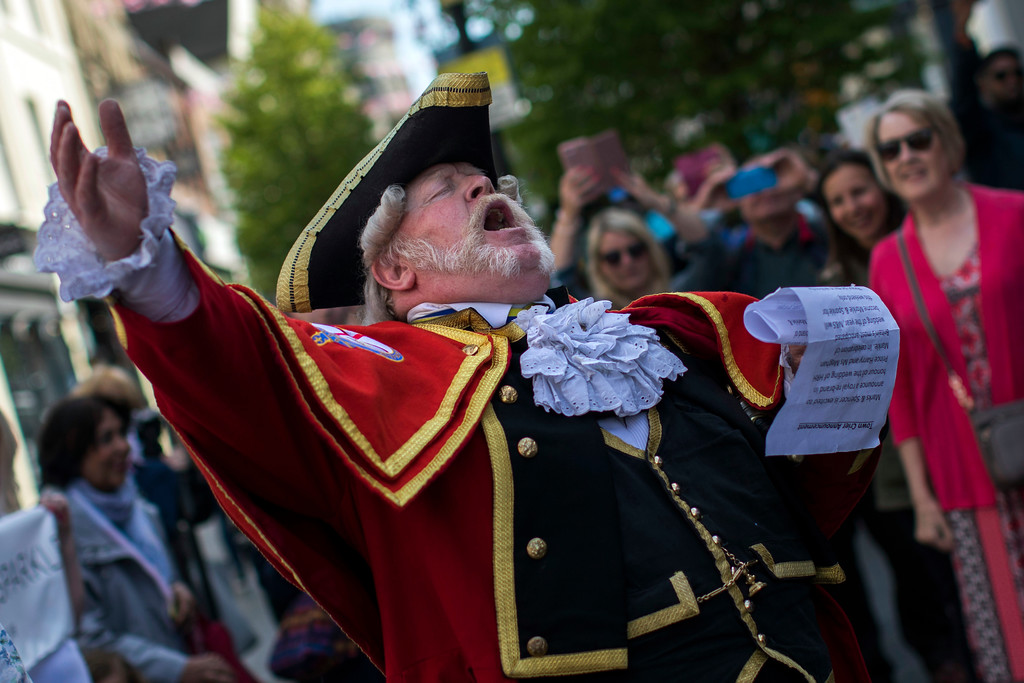 . A town crier announces the wedding to the crowd in Windsor, England, Friday, May 18, 2018. Preparations continue in Windsor ahead of the royal wedding of Britain\'s Prince Harry and Meghan Markle Saturday May 19. (AP Photo/Emilio Morenatti)