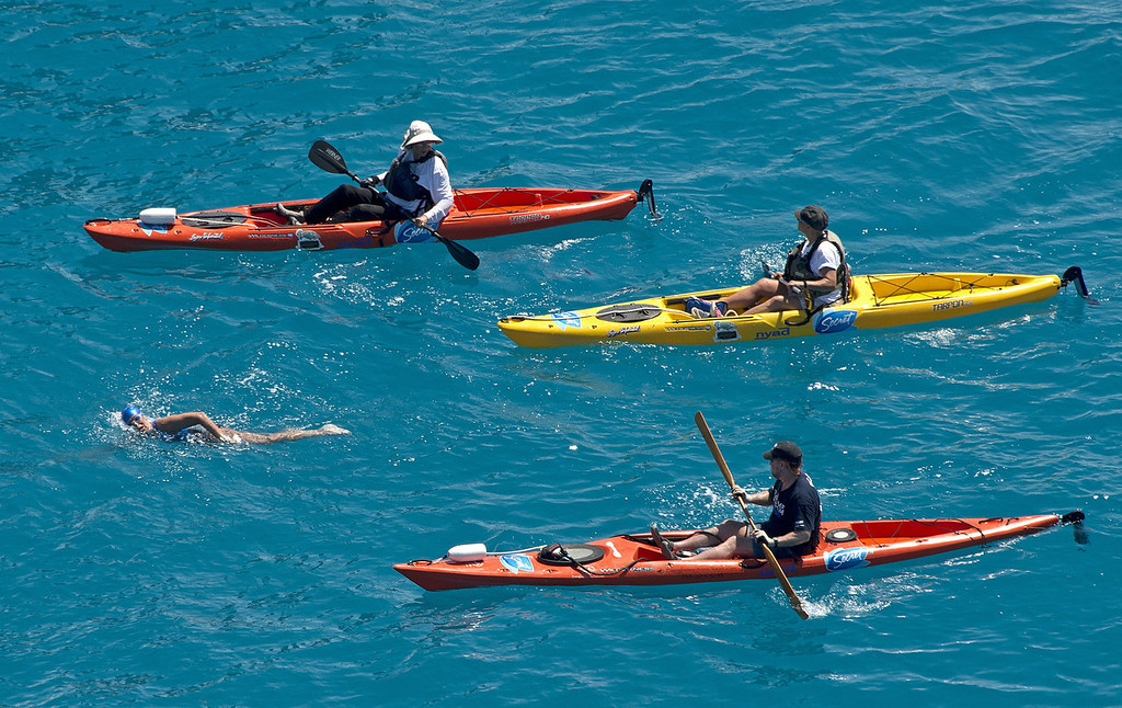. Diana Nyad, positioned about two miles off Key West, Fla., Monday, Sept. 2, 2013, is escorted by kayakers as she swims towards the completion of her approximately 110-mile trek from Cuba to the Florida Keys. Nyad, 64, is poised to be the first swimmer to cross the Florida Straits without the security of a shark cage.   (AP Photo/Florida Keys News Bureau, Andy Newman)