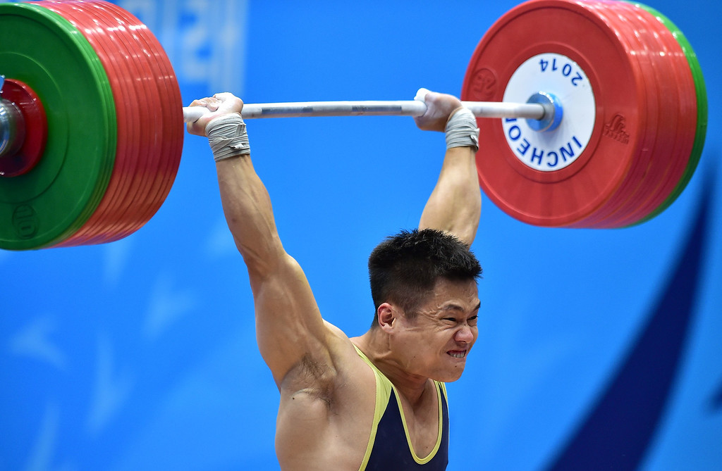 . China\'s Lyu Xiaojun attempts a lift in the clean and jerk of the men\'s 77kg weightlifting event during the 2014 Asian Games at the Moonlight Festival Garden in Incheon on September 23, 2014. JUNG YEON-JE/AFP/Getty Images