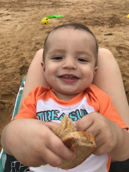 Asher offers to share his sandwich on the beach