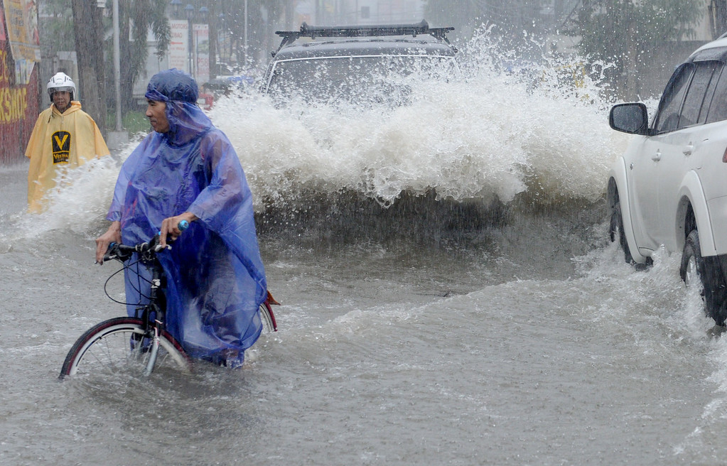. Commuters make their way through a flooded street in the suburbs of Manila on September 19, 2014. Heavy rains brought by the outer bands of Tropical Storm Fung-Wong shut down the Philippine capital on September 19, stranding motorists and forcing tens of thousands to flee their flooded homes, officials said.  JAY DIRECTO/AFP/Getty Images