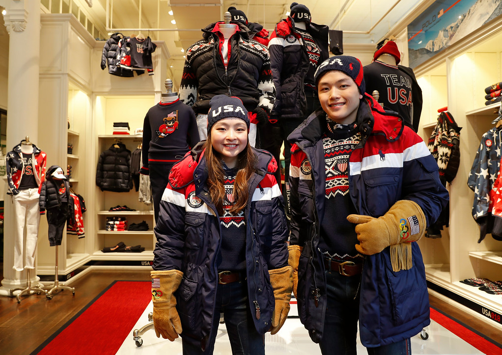 . Ice dancing pair Maia Shibutani, left, and Alex Shibutani, a brother and sister team, pose for photographs wearing Team USA Opening Ceremony uniforms designed by David Lauren for Polo Ralph Lauren, Monday, Jan. 22, 2018, outside the brand\'s Prince Street store in New York. The parkas have a battery-operated, built-in heating element that can be adjusted using a cell phone. The clothing will be worn at the upcoming Winter Olympics in South Korea. (AP Photo/Kathy Willens)