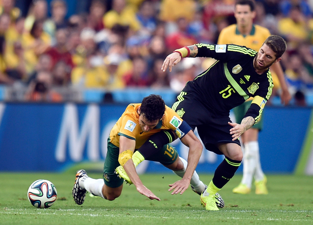 . Australia\'s Mile Jedinak, left, is sent tumbling by Spain\'s Sergio Ramos during the group B World Cup soccer match between Australia and Spain at the Arena da Baixada in Curitiba, Brazil, Monday, June 23, 2014. (AP Photo/Martin Meissner)