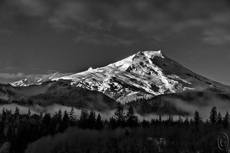 26 Jan 16.   Another MT Baker shot today for B&W Tuesday. While working with this image I got the idea that it might be capable of taking on an Adams look, so after I had finished rendering it in 5 different presentations, I returned to the B&W (1 of the 5) I had created and started playing with it. I intentionally limited my tools to that which were available in clarity, and spent most of my time working with the mid tones. I did have to employ a mask to keep my adjustments away from the triangular patch of ice on the left side near the summit, as that was on the edge of being blown out in the original capture, which was where it should have been. I also had to do some selective lightening of the trees in the foreground at the bottom of the frame, but the majority of my manipulation was on the mountain. I've neither added nor subtracted anything form the original shot, just played with the different zones of light to get the best contrast I could. It is not an Adams quality image, but I feel like I'm getting closer and am reasonably pleased with this attempt. You might enjoy playing with it to see if you can get it closer, perhaps making it a bit brighter.  I took the base image and added some small amount of detail enhancement to bring out the detail in the snow and the trees at the base of the shot, then converted it to a B&W, and then brought the B&W into Clarity to play with the tones. The adjustment to the mid tones account for the majority of the contrast in the image. Nikon D300s; 18 - 200; Aperture Priority; ISO 200; 1/640 sec @ f / 9.