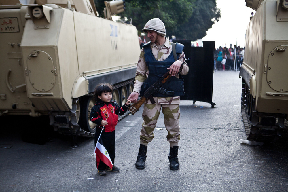 . An Egyptian soldier holds the hand of a child in Cairo\'s Tahrir Square during a rally marking the anniversary of the 2011 Arab Spring uprising on January 25, 2014. A spate of deadly bombings put Egyptian police on edge as supporters and opponents of the military-installed government take part in rival rallies for the anniversary of the 2011 Arab Spring uprising. (VIRGINIE NGUYEN HOANG/AFP/Getty Images)
