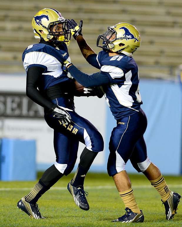 . Muir \'s Tony Claxton (21) celebrates Daniels Cervantes (5)  first touchdown of the annual Turkey Tussle against Pasadena Friday night, November 8, 2013 at the Rose Bowl in Pasadena. (Photo by Sarah Reingewirtz/Pasadena Star-News)