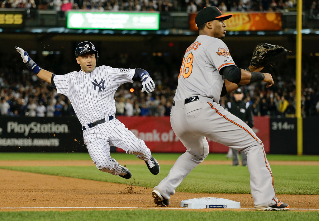 . New York Yankees\' Derek Jeter steals third base against the Baltimore Orioles in the first inning of a baseball game, Thursday, Sept. 25, 2014, in New York. At right is Orioles third baseman Jimmy Paredes. (AP Photo/Julie Jacobson)