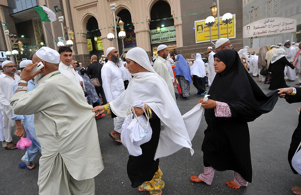 . Muslim pilgrims walk in a group to perform evening prayers in Mecca\'s Grand Mosque on October 8, 2013, as more than two million Muslims have arrived in the holy city for the annual hajj pilgrimage. The hajj, which is one of the world\'s largest human assembly, begins on October 13 amid concerns over the deadly MERS coronavirus. (FAYEZ NURELDINE/AFP/Getty Images)
