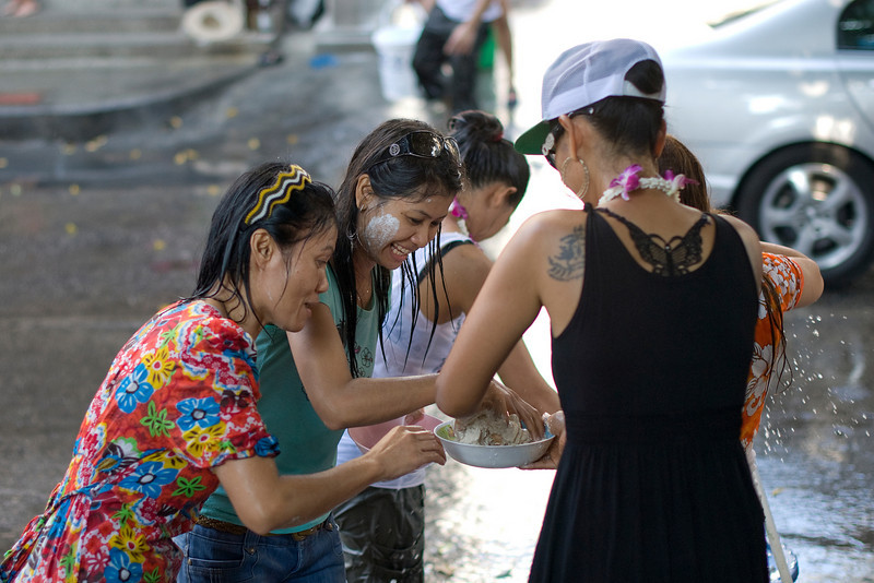 Women grabbing onto a bowl of paint during the 2010 Songkran Festival