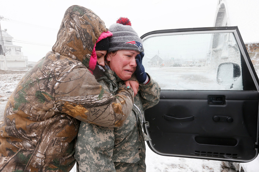 . Taylor Millar, left, hugs her friend Jennifer Bruno, after Bruno was forced to vacate her house when it was heavily damaged by ocean waves in a winter storm, Tuesday, Jan. 27, 2015, in Marshfield, Mass. The storm has punched out a section of the seawall in the coastal town of Marshfield, police said. (AP Photo/Michael Dwyer)