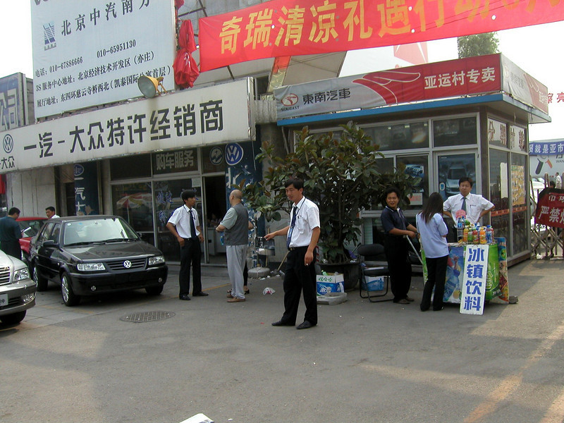 prowling sales men, Beijing car dealership, June 2004