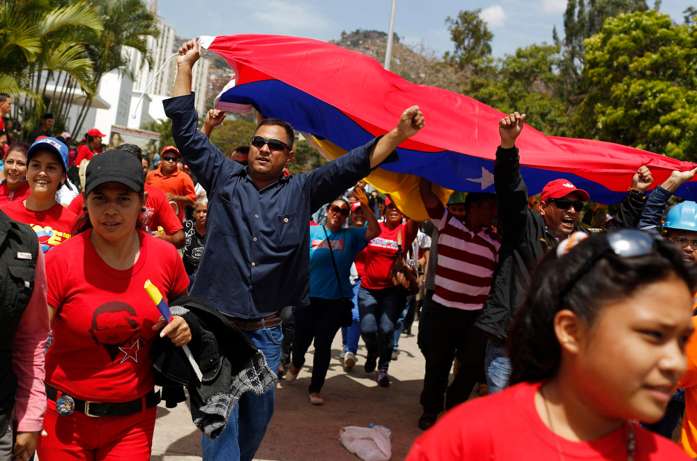 . Supporters of Venezuela\'s late President Hugo Chavez run to get a place in line to view his body in state at the Military Academy in Caracas on March 7, 2013. Venezuelans flocked to pay tribute to Chavez two days after he died of cancer.  REUTERS/Tomas Bravo