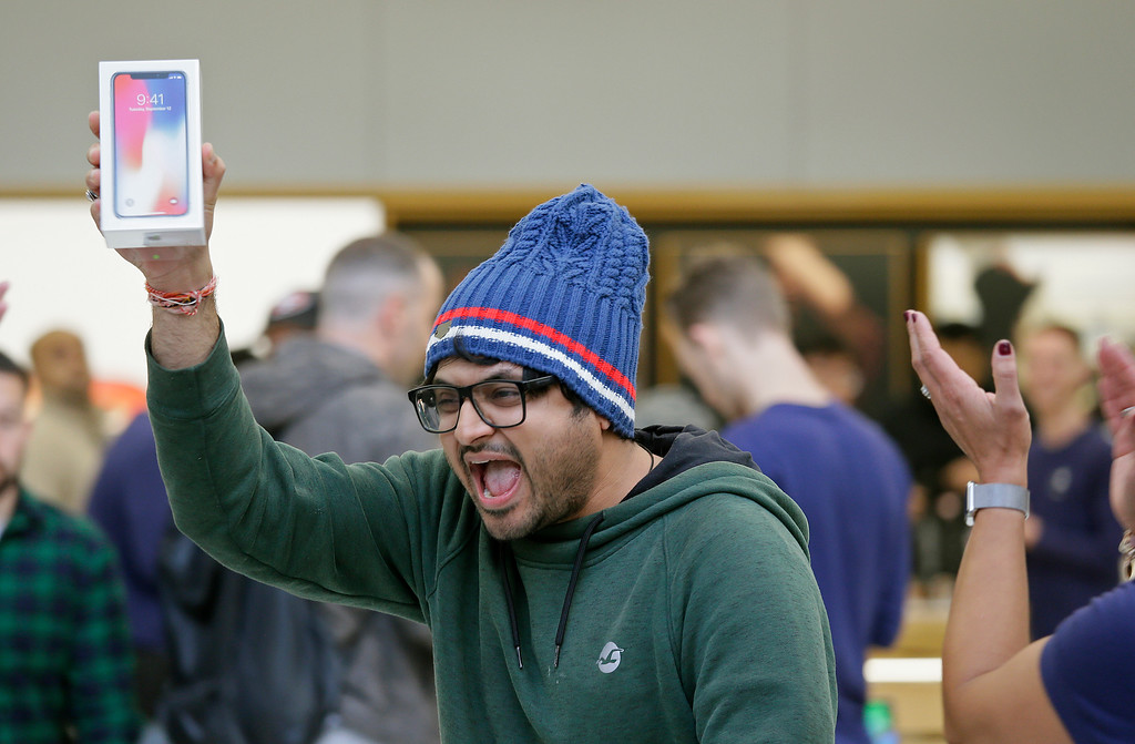 . Shalin Mobi, of India, reacts after being the first person to purchase the new iPhone X at the Apple Union Square store Friday, Nov. 3, 2017, in San Francisco. AP Photo/Eric Risberg)
