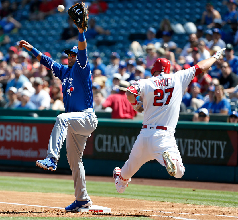 . Toronto Blue Jays first baseman Edwin Encarnacion reaches for a ball off Los Angeles Angels\' Mike Trout (27) who grounded out to third in the first inning of a baseball game in Anaheim, Calif., Sunday, Sept. 18, 2016. (AP Photo/Christine Cotter)