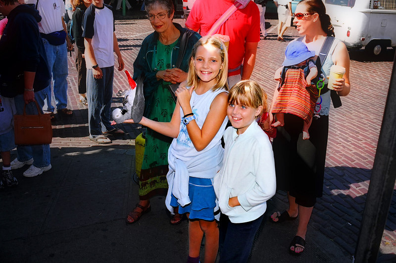 Emily and Elena near Pike's Place - do you see the (live) parrot, curled upside down on Emily's hand??