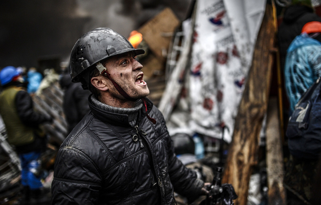 """. A protester stands behind barricades during clashes with police on February 20, 2014 in Kiev. Ukraine\'s embattled leader announced a \""""truce\"""" with the opposition as he prepared to get grilled by visiting EU diplomats over clashes that killed 26 and left the government facing diplomatic isolation. AFP PHOTO / BULENT KILIC/AFP/Getty Images"""