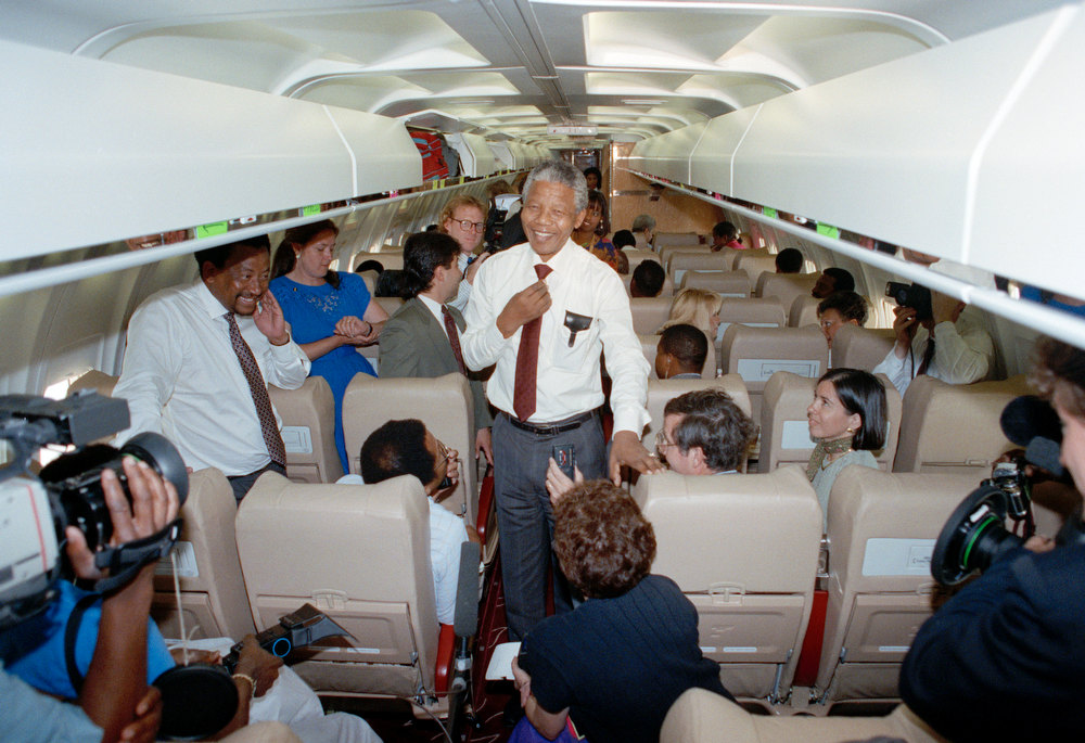 ". Nelson Mandela chats with members of the news media aboard his chartered fight from Washington D.C. to Atlanta Wednesday, June 27, 1990. Referring to his arduous travel schedule Mandela said, ""I feel as well as I should for my age. And of course the warm reception we have received has given us a feeling of well being.\"" (AP Photo/David Longstreath)"