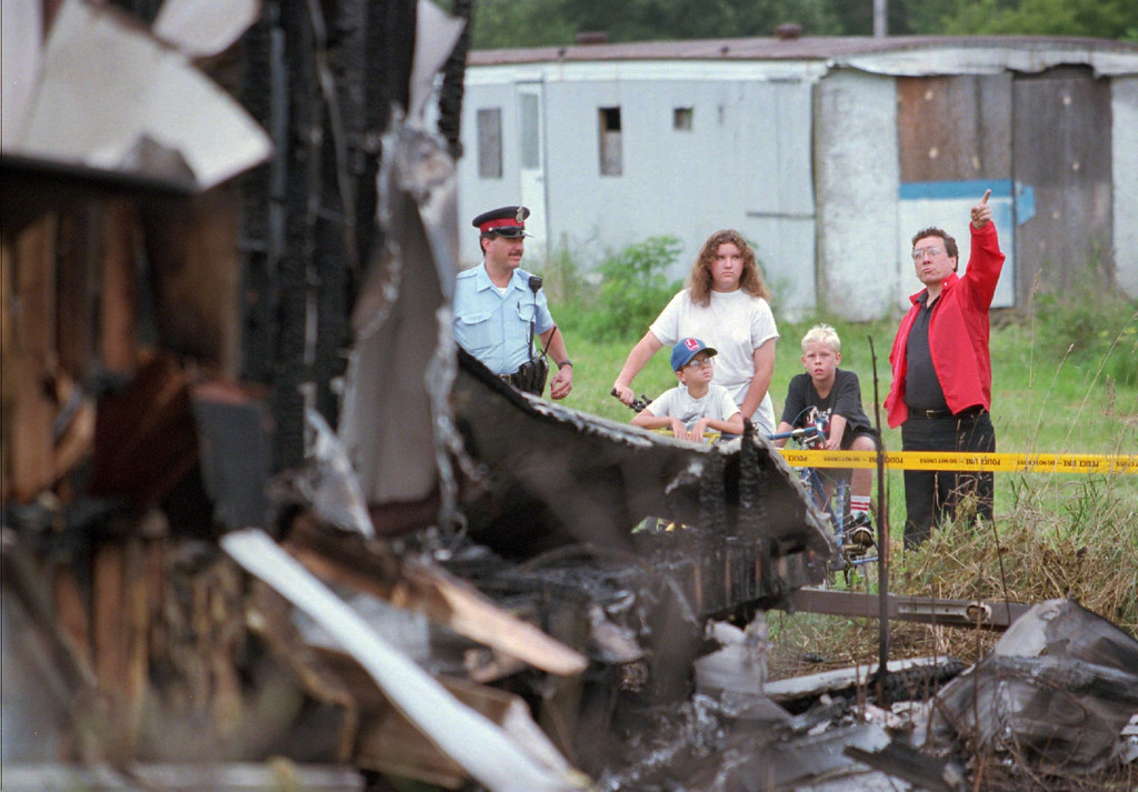 . John Stephenson, right, points toward the sky as he and others examine the wreckage of a mobile home apparently destroyed by a meteor in Windsor, Ontario early Friday, morning, Aug. 25, 1995. Windsor police said a chunk of the meteor slammed into the vacant mobile home, burning it to the ground. No injuries were reported. Others in photo are Windsor police Sgt. Joseph Monteleone, left, Tanya Neufeld, 12, her brother, Kevin, 11, and Matthew Breault, 11, all residents of the park. (AP Photo/Tom Pidgeon)